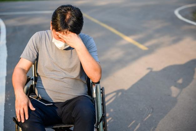アジアの老人障害者は歩くことができません。車椅子に座っている、または公園の車椅子に座っている悲しいことに車椅子に座っている