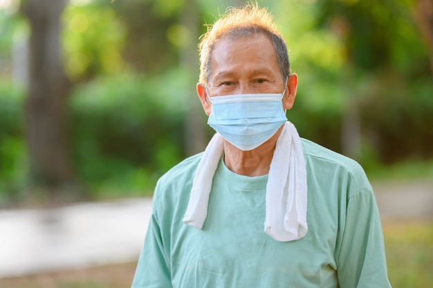 Asian elderly man or senior male wearing a medical mask prevention of viruses and sickness in outdoor exercise and walking in the park. Premium Photo