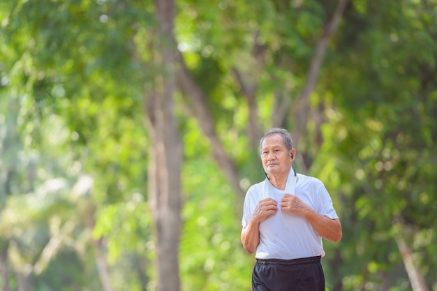 Asian elderly man or senior runner smile happily in jogging outdoor and walking workouts in the park.
