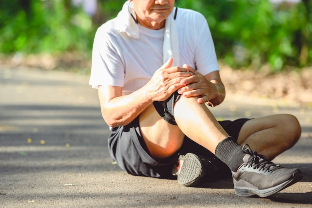 Asian elderly man or senior runner stop running because of a knee injury. and put a hand on the knee that was hurt from running outdoors and walking in the park.
