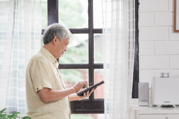 Asian elderly man using tablet checking social media near window in living room at home. lifestyle senior men at home concept.