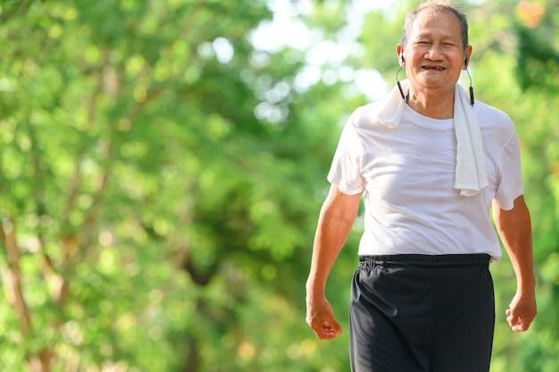 Asian elderly men or senior runners smile happily on outdoor walks and exercise walks in the park.