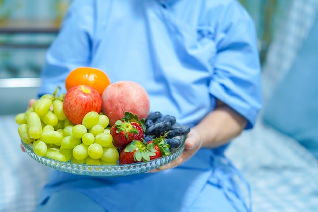 Asian elderly old lady woman patient holding fruits healthy food with hope happy in hospit