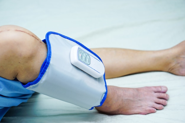Asian elderly old woman patient with cordless air compression pressure leg massage in hosp
