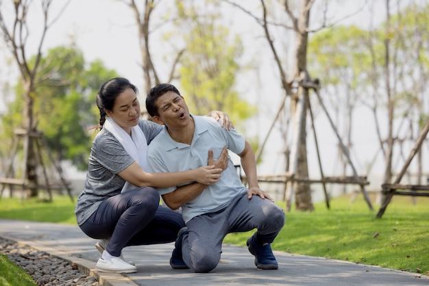 運動中に公園の床に倒れるアジアの高齢者や老人の事故は、膝の痛みを伴う。
