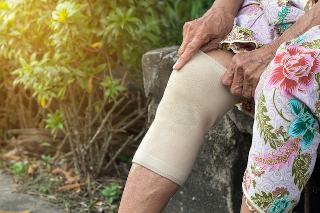 Asian elderly people or older woman wearing the knee support