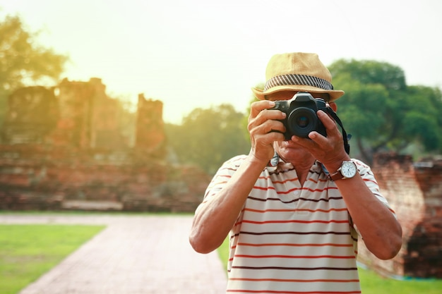 Asian elderly travelers hold camera on ancient world heritage palace in ayutthaya.