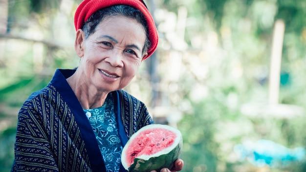 自然の果物を楽しく食べるアジアの高齢女性。高齢者のための自然健康食品の概念