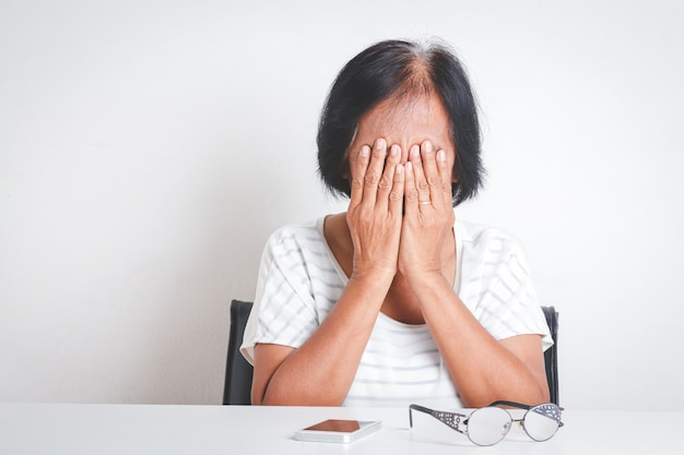 Asian elderly woman have stress feeling very worried about problems with retirement life.