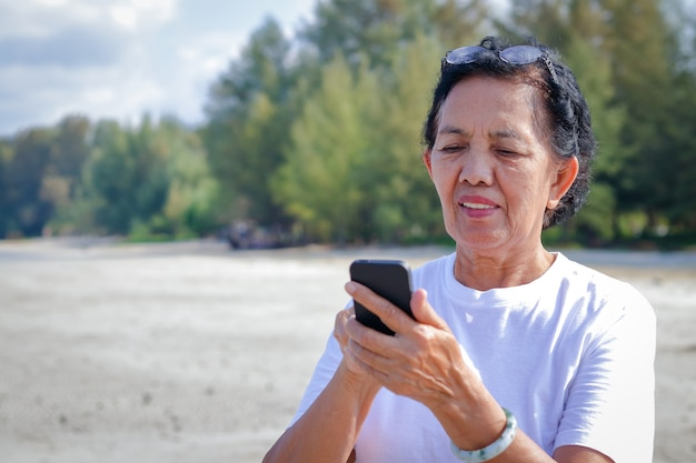 An asian elderly woman holding a phone to take pictures at the sea