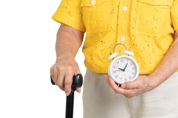 Asian elderly woman holding a white alarm clock and walking stick
