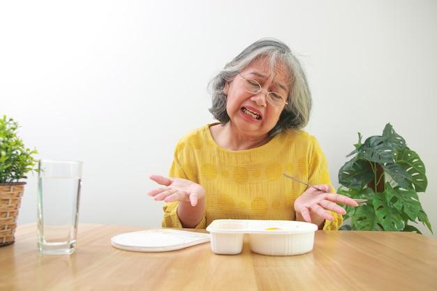 집에 있는 아시아 노인 여성 코로나바이러스 전염병 동안 그녀는 상자 음식의 지루함처럼 먹고 있습니다. covid-19 바이러스 감염 예방의 개념