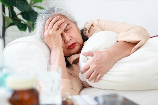 거실 소파에 누워 아픈 아시아 할머니 그녀는 큰 두통을 가졌습니다. 가정 치료, 노인 건강 관리의 개념