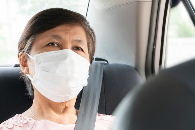 アジアの高齢者の女性の乗客は、車に座っているときにコロナウイルスやcovid-19を防ぐためにサージカルマスクを着用します。公共交通機関におけるパンデミックウイルス。