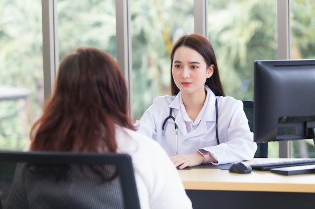 아시아 노인 여성 환자는 두 사람 모두 의료용 얼굴 마스크를 착용하는 동안 설명하는 의사에 의해 건강을 확인합니다