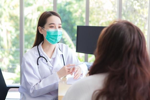 아시아 노인 여성 환자는 병원에서 두 사람 모두 얼굴 마스크를 착용하는 동안 의사의 건강을 확인합니다