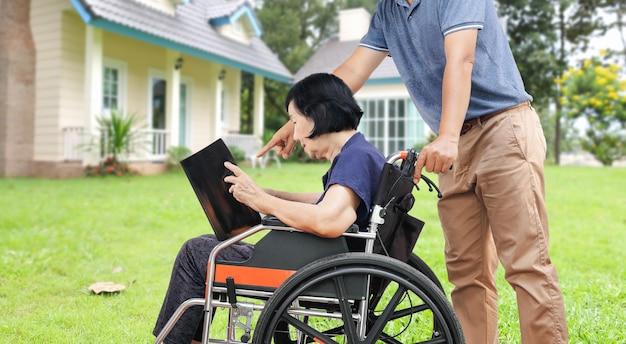 Азиатская пожилая женщина, читающая книгу со своим сыном, заботится на заднем дворе