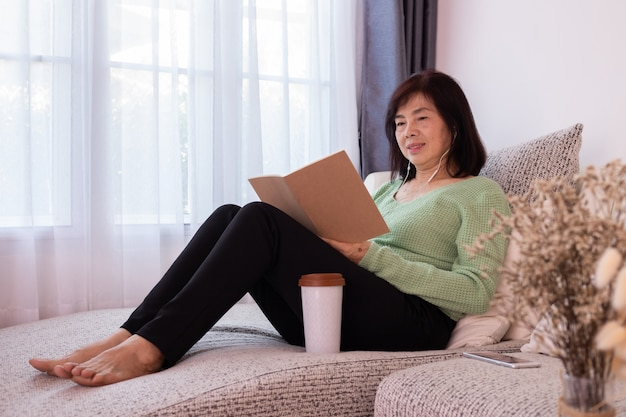 Asian elderly woman reading a book on couches in living room.