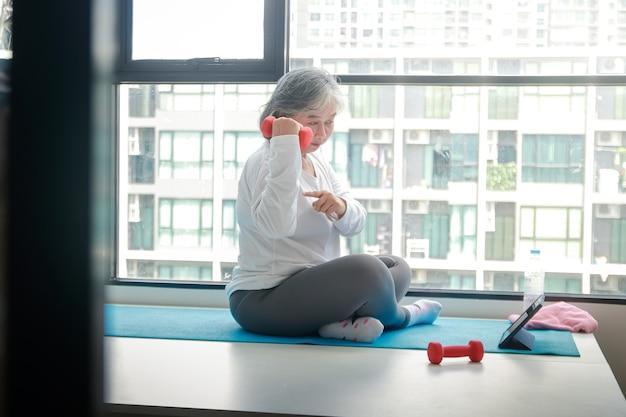 아시아 노인 여성은 태블릿을 통해 화상 통화를 통해 온라인 피트니스 교사에 따라 집에서 운동을 하고 요가 포즈를 취합니다. 사회적 거리두기, 노인 건강 지키기