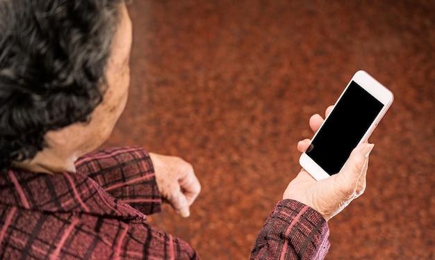 아시아 노인 여성 앉아서 스마트 폰보고