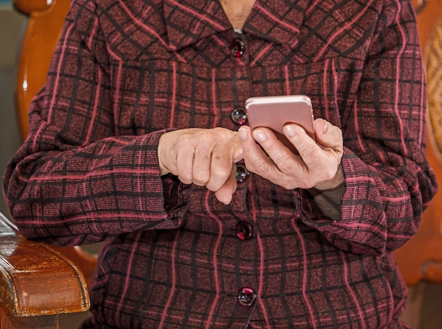 Asian elderly woman sitting and looking through something on modern smartphone, making connection with others at home, living technology, close up