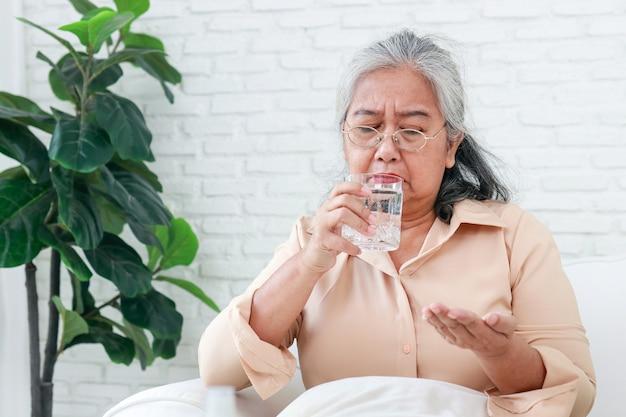 집에 있는 아시아 할머니 그녀는 독감에 걸렸습니다. 그녀는 진통제를 먹고 일반 물을 마시고 있습니다. 노인 질병의 개념입니다. covid-19 동안 노인 돌보기