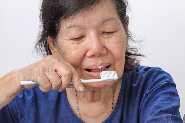 Азиатская пожилая женщина пытается использовать зубную щетку, тремор рук. здоровье зубов