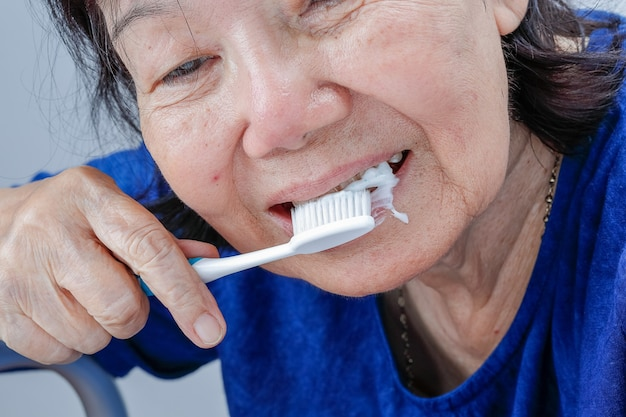 Asian elderly woman trying use toothbrush ,hand tremor . dental health