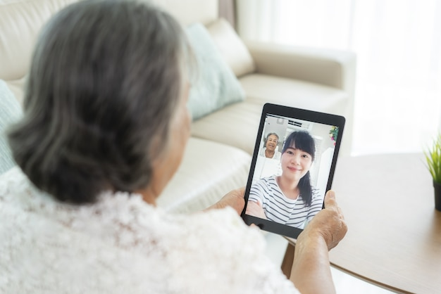 Asian elderly woman virtual happy hour meeting and talking online together with her daughter