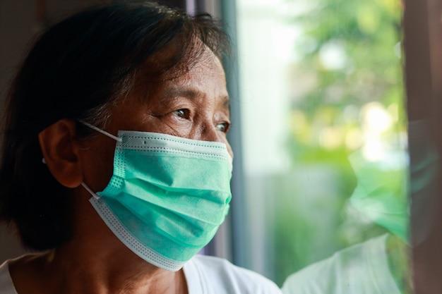 自宅に住む仮面をかぶったアジアの老婆家の前に立って外を眺めていると、自分を拘束するのに飽き飽きしている。家の隔離、社会的距離、コロナウイルス予防