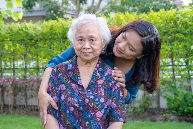 自然公園で幸せに歩いている介護者とアジアの年配の女性。