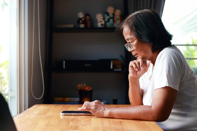 아시아 노인 여성은 집에 살고 있습니다. 코로나바이러스 전염병 동안 온라인으로 스마트폰을 보고 친구들과 채팅했습니다. 자가격리, 자택격리도 지겹고,