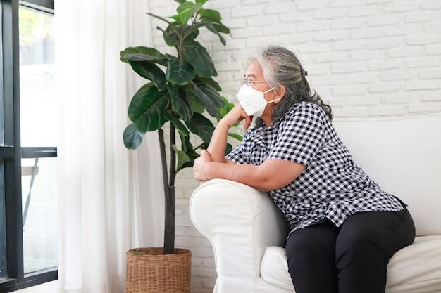 マスクをかぶったアジアの年配の女性彼女は家のソファーに孤独に座っていた。 covid-19パンデミックの間、自宅で自分の世話をします。コロナウイルス感染を防ぐためのセルフケア、自宅隔離