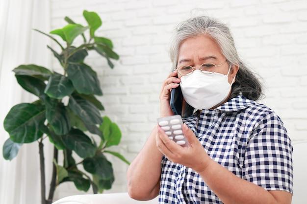 마스크를 쓴 아시아 노인 여성 그녀는 스마트폰으로 의사와 병에 대한 약 복용에 대해 이야기합니다. covid-19 전염병 동안 집에서 자신을 돌보십시오. 가정 격리