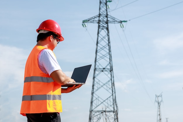 アジアの電気技師は、発電所に立っている可動装置を使用して標準の安全制服を着て、高圧電柱の検査を行っています。