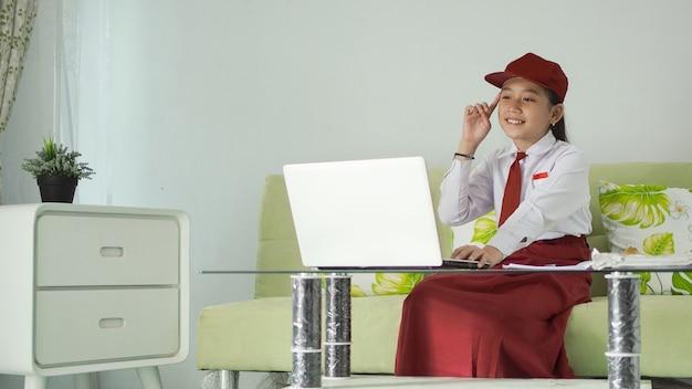 Азиатская девочка начальной школы находит идеи с ноутбука дома