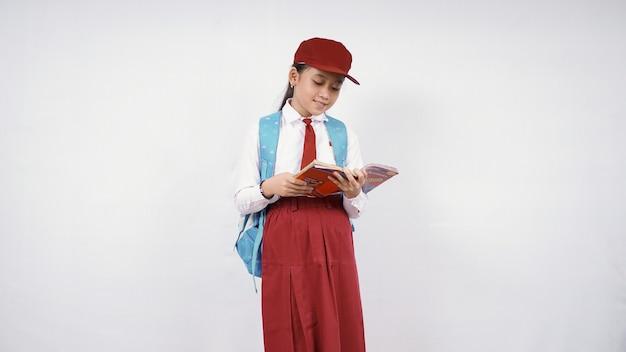 Азиатская девочка начальной школы читает книгу, счастливо изолированную на белом фоне