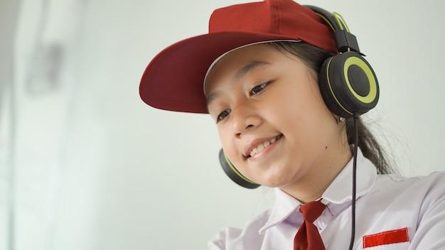 自宅で楽しくオンラインで勉強しているアジアの小学生の女の子