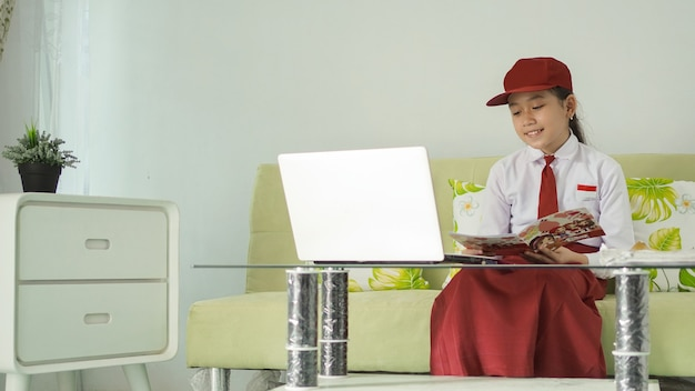 Asian elementary school girl studying online from home reading books happily