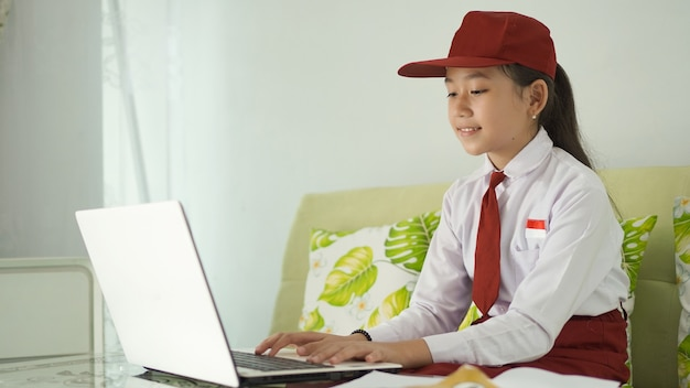 Asian elementary school girl studying online from home typing on laptop
