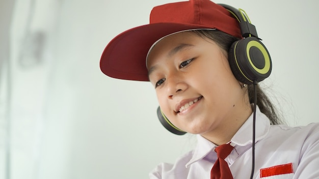 Asian elementary school girl studying online at home happily Premium Photo
