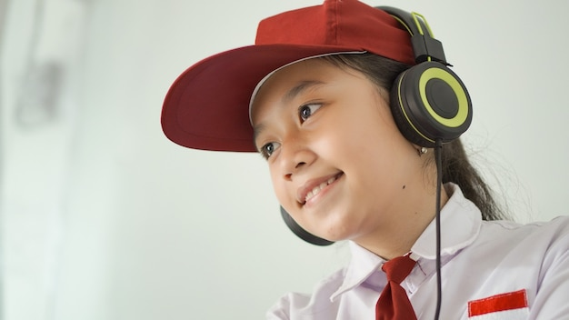 Asian elementary school girl studying online at home happily