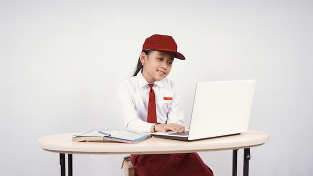 Asian elementary school girl studying online using laptop isolated on white background