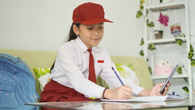 Asian elementary school girl writing ideas from her smartphone into a book at home