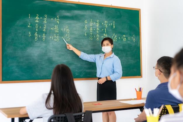 アジアの小学生と教師が衛生的なマスクを着用