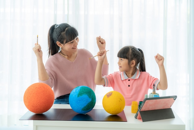 Asian elementary schoolgirl with mother painting the moon in science class