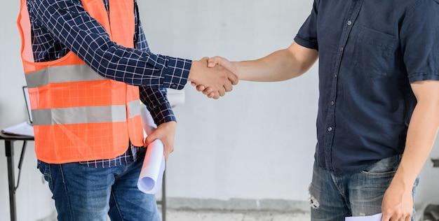 建設不動産サイトでのアジアのエンジニアと建築家の握手。チームワークと成功した住宅団地建設プロジェクト
