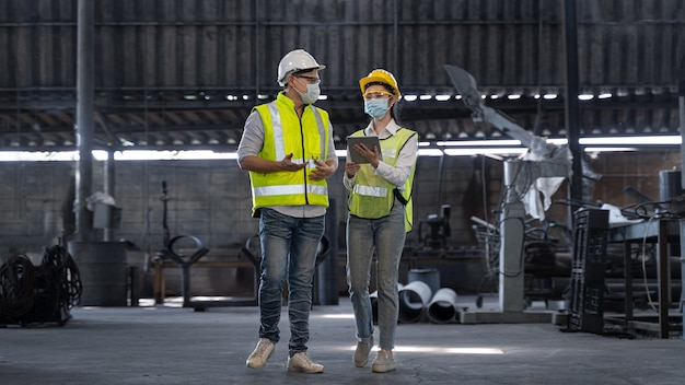 Asian engineer checking production process on factory station by wearing safety mask to protect for pollution and virus in factory during covid-19 pandemi