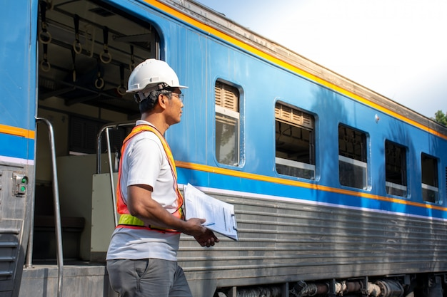 Asian engineer checking train for maintenance in station