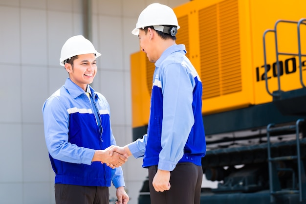 Asian engineer having agreement handshake at construction machinery of construction site